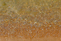 Wave Transparent Sea Water over Sand beach with Small Pebbles background