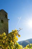 A plane with contrails flies over the castle ruins Are in the back light of the sun.