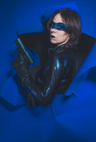 Killer, Brunette girl dressed in leather and latex fitted with pistol on blue background