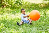 Afrikanischer Junge spielt mit einem Hüpfball