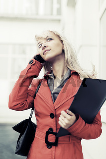 Blond business woman calling on the cell phone against office building