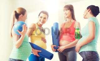group of happy pregnant women talking in gym