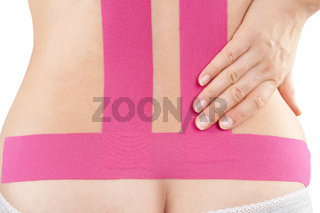 Pink therapeutic tape on female back.