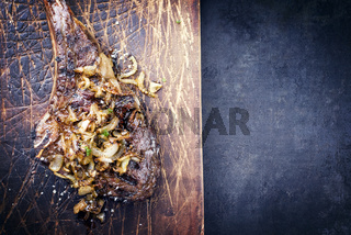 Barbecue dry aged wagyu tomahawk steak as close-up on old wooden board with copy space on the right