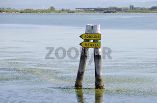 Pfähle mit Wegschildern als Fahrwassermarkierung in der Lagune von Grado