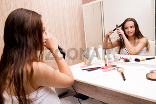 Pretty woman doing her hair preparing for party