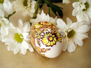beautiful easter egg with white flowers on golden background