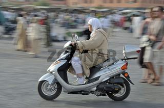 Marokkanerin fährt auf einem Moped, Djemaa El Fna, Medina, Altstadt, UNESCO-Weltkulturerbe, Marrakesch, Marokko, Afrika