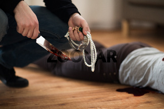 criminal with knife and jewelry at crime scene