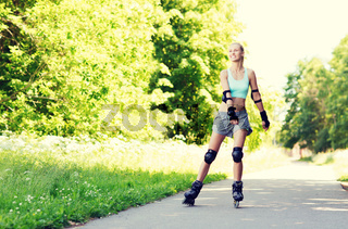 happy young woman in rollerblades riding outdoors
