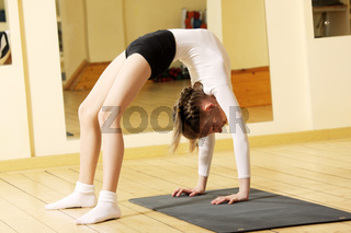Little gymnast girl making bridge stand