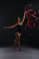 Studio photo of sexy brunette dancing with ribbon