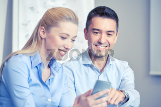 smiling businesspeople with smartphones in office