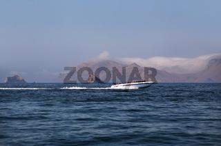 Tourists riding in a boat in Ballestas Islands Reserve in Peru
