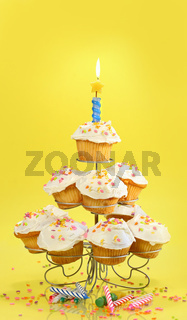 Cupcakes with blue candle on yellow