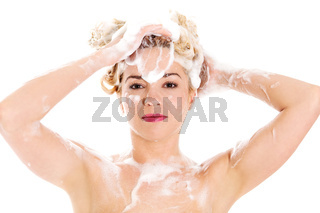 Beautiful smiling young woman washing her hair with shampoo - isolated on white.