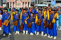 Mitglieder eines traditionellen Jugendorchesters in Deel-Kleidung und mit Pferdekopfgeige