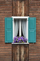 Window with green shutters, curtains and potted flowers on the window frame, Saas-Fee, Valais