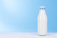 Flasche Milch auf hell blauem Hintergrund.