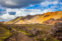 Travel to Iceland in July, volcanic summer tundra. Multi-colored rhyolite mountains - orange, yellow, green and blue