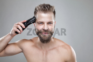Handsome bearded man cutting his own hair with a clipper