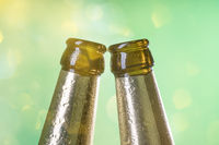 two beer bottle necks with green background