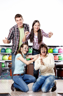 Four young friends rejoice to a successful throw in bowling