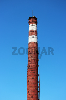 Brick red with white stripes trumpet on a cloudless blue sky.