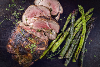 Barbecue Lamb Roast with green Asparagus as close-up on an old metal sheet