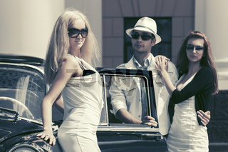 Young fashion people next to vintage car in city street