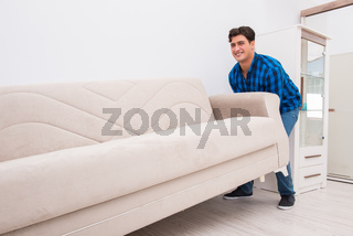 Young man moving sofa couch