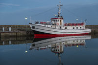 A white ship is reflected in the evening in the still water at the pier.