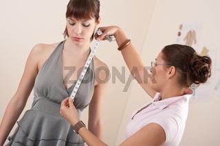 Female fashion designer measuring model for fitting