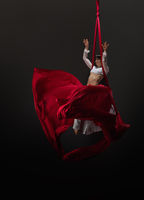 Pretty young gymnast on red aerial silks in studio