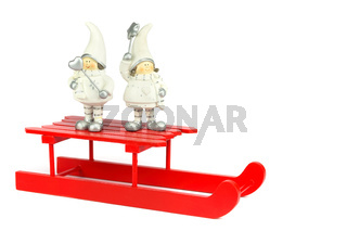Children christmas figurines on red sleigh
