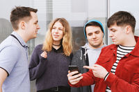 group of teenage friends having a conversation while young man is showing something on his smartphone