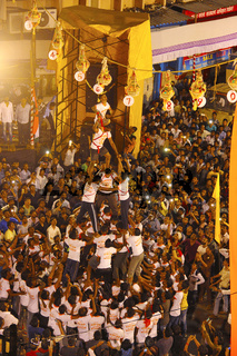 Govindas, young boys surrounded by crowd, making human pyramid to break Dahi Handi