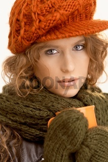 Attractive girl dressed up warm drinking tea