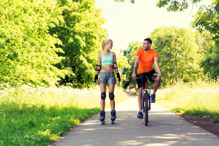 happy couple with roller skates and bicycle riding