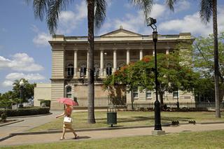 Frau mit Schirm im Park Queens Gardens vor dem Gebaeude der old State Library in Brisbane