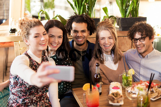 friends taking selfie by smartphone at bar or cafe