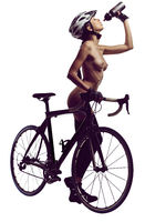 Naked woman with a bicycle, drinking a water. Studio shot, isolated on a white background