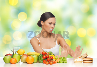 woman with fruits rejecting fast food on table