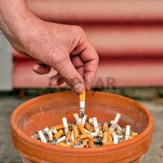 Zigarette wird in einem  Aschenbecher ausgedrückt