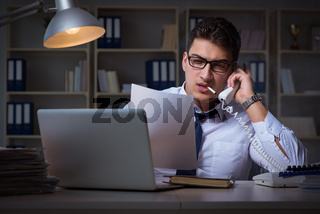 The businessman speaking on phone and smoking in office
