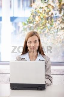 Portrait of confident businesswoman with laptop