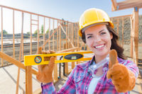 Female Construction Worker with Thumbs Up Holding Level Wearing Gloves, Hard Hat and Protective Goggles at Construction Site