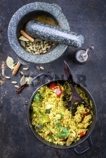 Indian Vegetable Biryani with Sweet Pepers and Zucchini as close-up in a frying pan