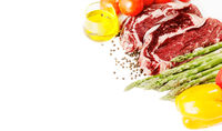 Raw steaks and vegetables