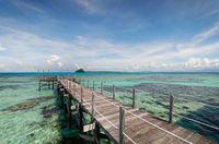 Wooden pier extends over shallow sea.